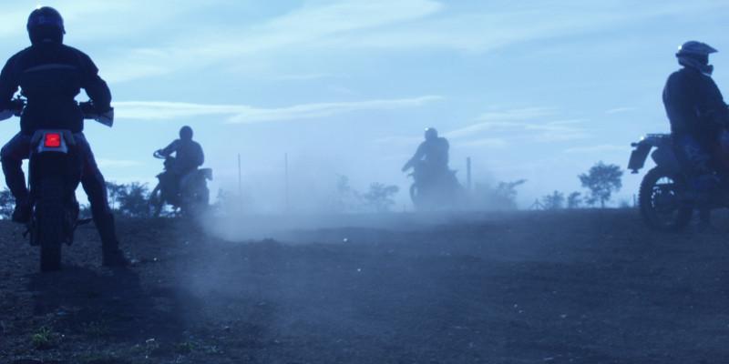 Vier Motorradfahrer im Gelände. Um sie herum Abgase.