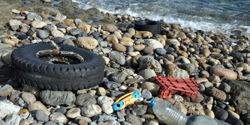 Plastikreste am Meer: Ein alter Reifen, eine Flasche, Kinderspielzeug und der Rest eines Einkaufkorbs aus Plastik liegen auf einem Kiesstrand.