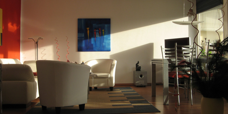 livingroom with armchairs, dining table, carpet, lamps, pictures and potted plants