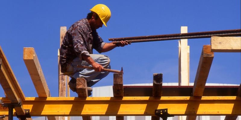 Ein Bauarbeiter mit gelbem Helm verschalt eine Decke.