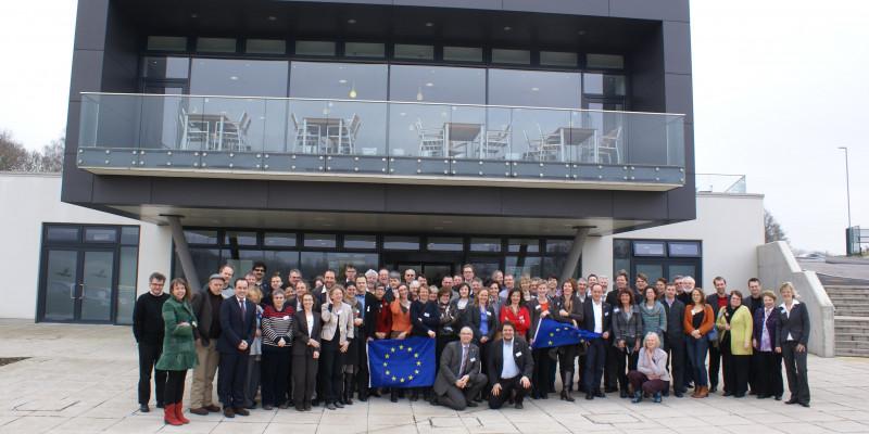 Personengruppe mit EU-Fahne im Hintergrund ein Haus