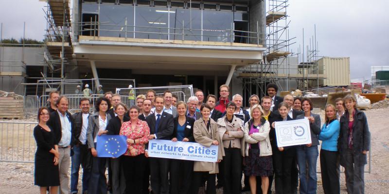 Viele Personen vor einem Haus im Bau, die die EU-Fahne und das Future Cities-Logo hochhalten