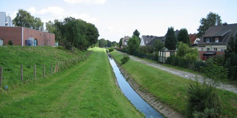 Ein Bach fließt im Grünen am Ortsrand entlang
