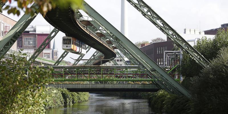 Schwebebahn fährt über einen Fluss, rundum ist Stahlkonstruktion zu sehen.