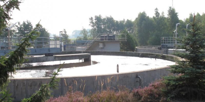 In einem großen runden Behälter aus Beton befindet sich Wasser. Der Behälter steht in der freien Natur.