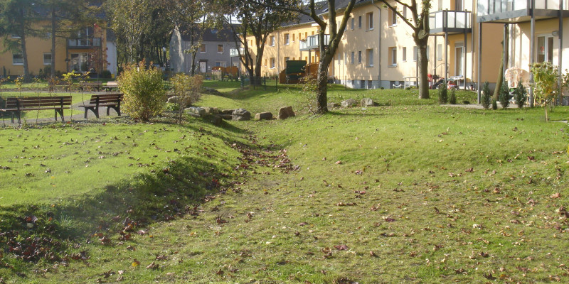 Auf dem Rasenboden verlaufen Rinnen für Regenwasserabfluss. Im Hintergrund stehen Wohnhäuser mit Balkonen und Terassen zum Rasen hin.