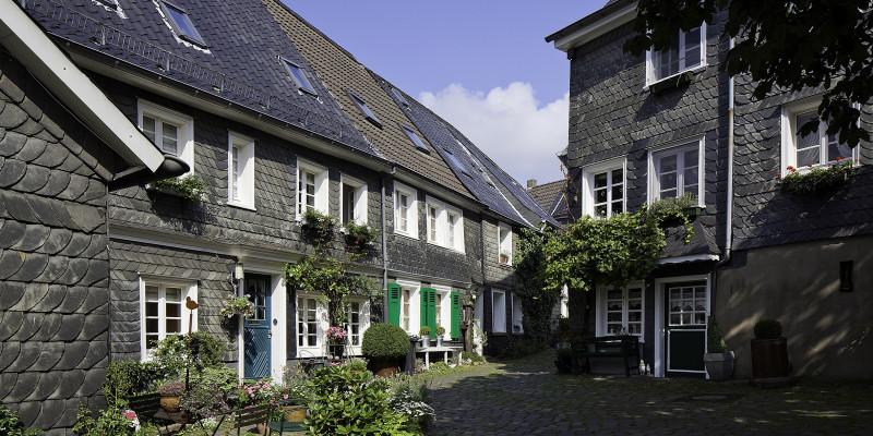 Zu sehen ist ein Ausschnit des Ortes Solingen. Zwei grauweiße Gebäude stehen schräg zu einander. Der blaue Himmel ist im Hintergrund oben zu sehen.