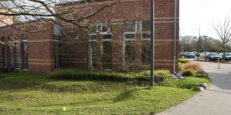 Auf dem Rasenboden verlaufen Rinnen für Regenwasserabfluss. Im Hintergrund steht ein rotes Backsteingebäude und dahinter ein Parkplatz mit Autos.