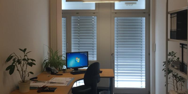 Ein Büro mit Schreibtisch und Stuhl mit zwei großen Fenstern und Sonnenrollos