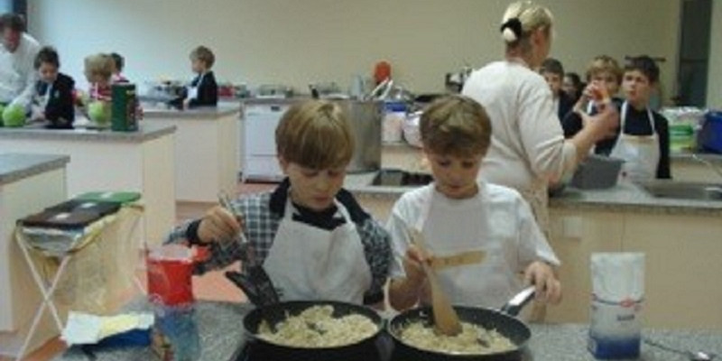 Kinder stehen am Herd und kochen Äpfel ein. Im Hintergrund kochen weitere  Kinder mit verschieden anderen Produkte aus der Region. Lehrerin geht herum und beantwortet Fragen.
