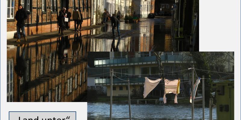 Wasser überflutet die Straße in der historischen Altstadt. Am linken Bildrand bewegen sich Menschen auf dem verbliebenen schmalen Bürgersteig vor den Altstadtfassaden. Auf der rechten Seite säumen Bäume und Laternen die Straße. Im Vordergrund rechts sieht man zum Trocknen aufgehängte Wäsche auf einem Wäscheständer tief im Wasser stehend, im Hintergrund befindet sich ein modernes Wohnhaus.