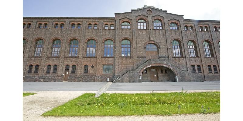 Ansicht eines Gebäudes aus Backstein mit Rasenstreifen im Vordergrund: Das Industriedenkmal Maschinenhalle Zweckel.