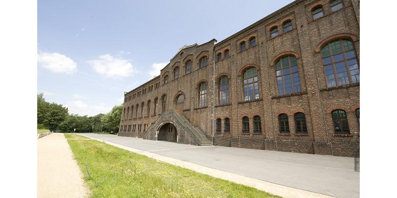 Ansicht eines Gebäudes aus Backstein mit Rasenstreifen im Vordergrund. Das Industriedenkmal Maschinenhalle Zweckel.