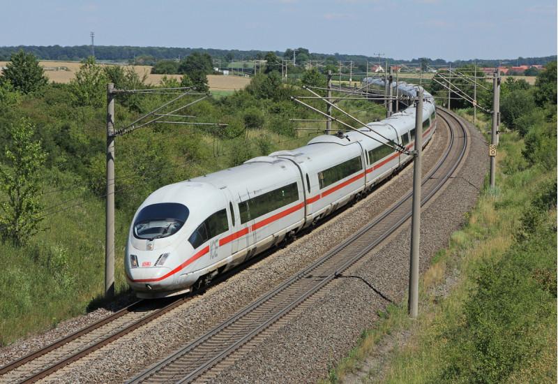 Das Bild zeigt einen fahrenden ICE 3 der Deutschen Bahn AG in ländlicher Umgebung.