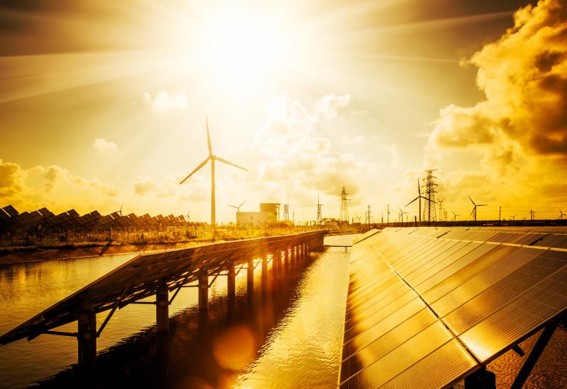 Das Bild zeigt im Vordergrund eine Solaranlage und im Hintergrund Windräder im Sonnenuntergang.