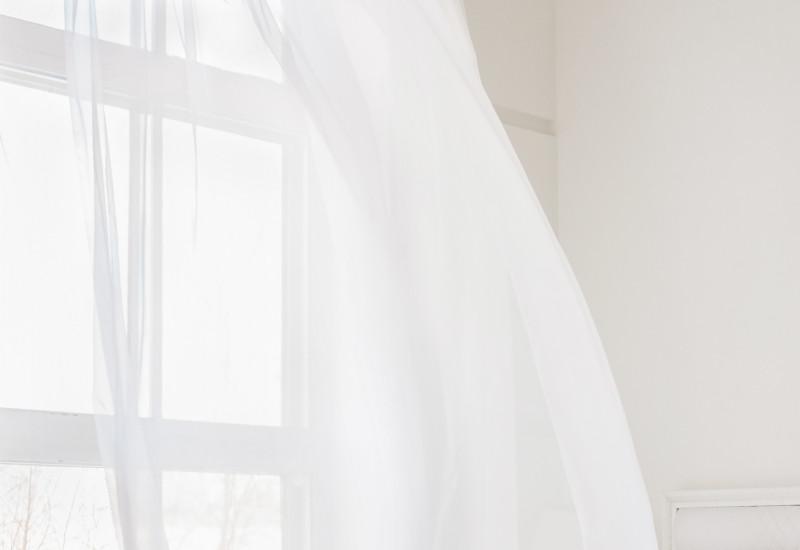 Lüften eines Schlafzimmers: der Vorhang weht über das Bett.