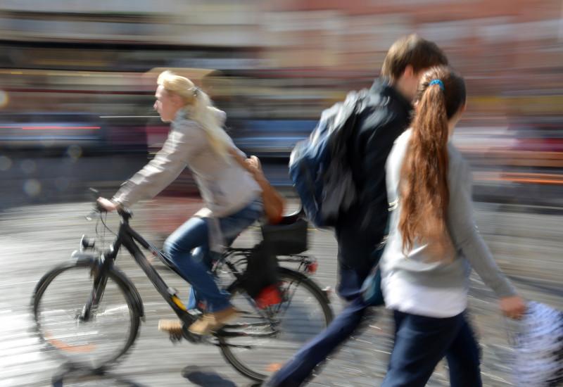 Fußgänger und Radfahrerin in einer Stadt.