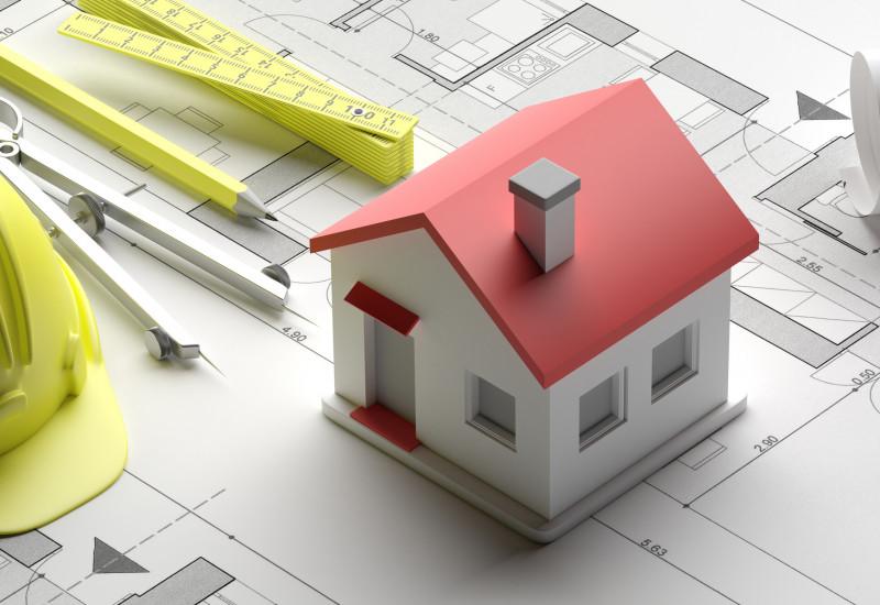 Das Bild zeigt einen Bauplan und ein Modell für ein Eigenheim sowie Zirkel, Bleistift, Zollstock und Schutzhelm.