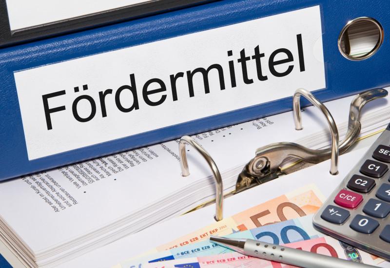"""Foto: Aktenordner mit Beschriftung """"Fördermittel"""", davor auf einem Tisch liegen Geld, Taschenrechner und Kugelschreiber."""