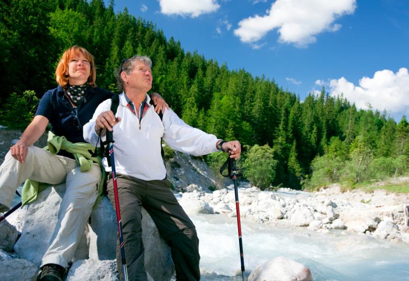Foto: Ein älteres Paar mit Wanderstöcken sitzt auf einem Felsblock direkt an einem Gebirgsfluss.