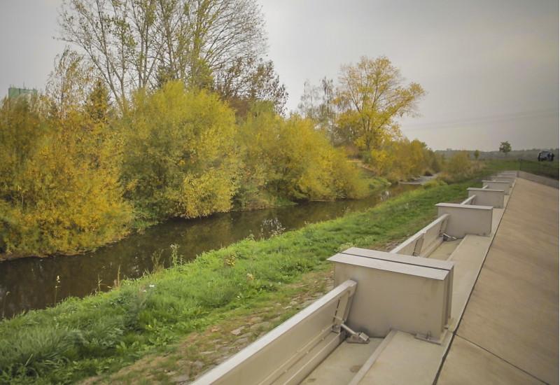 Foto: Ein Klappenwehr aus Beton und Stahl entlang der Helme. Das Ufer im Bereich vor dem Klappenwehr ist mit Gräsern bedeckt. Die andere Uferseite ist naturnah mit Gehölzen bestanden.