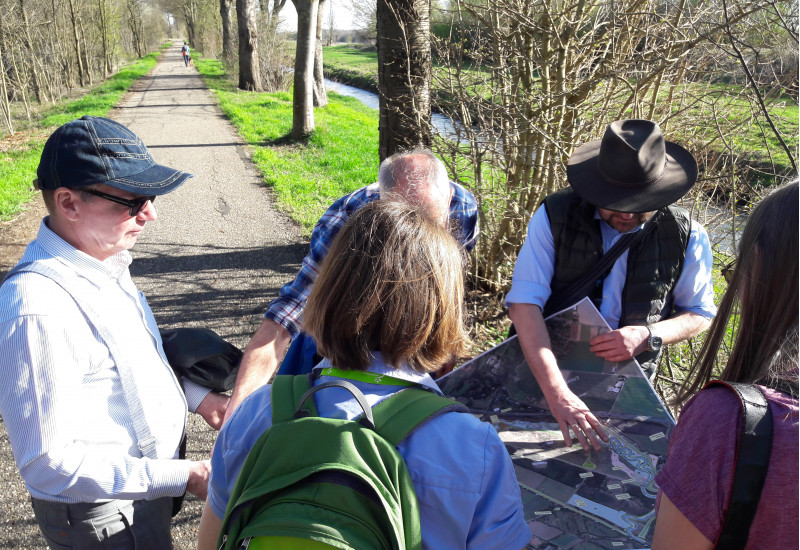 Foto: Mehrere Personen blicken vor einem technisch ausgebauten Fluss auf Planungsunterlagen.