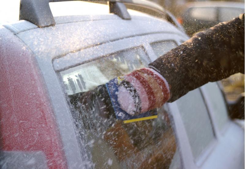 Autoscheibe wird von Eis freigekratzt