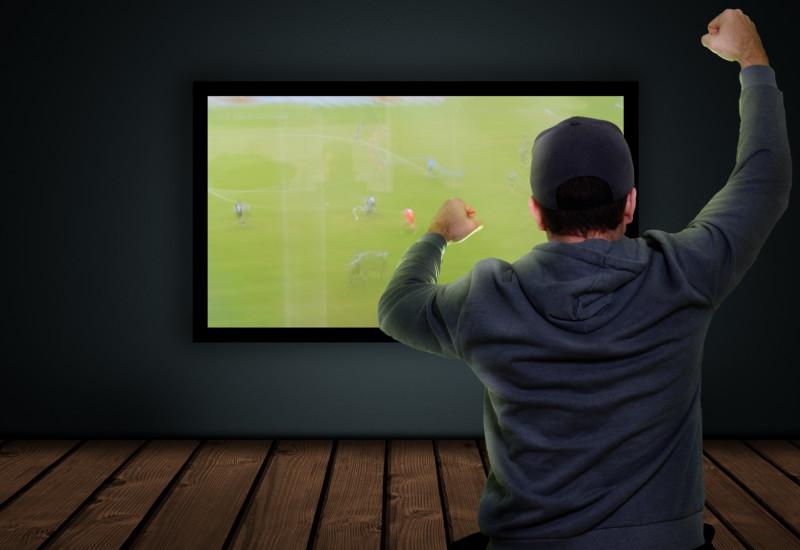 Mann schaut auf Flachbildfernseher ein Fußballspiel