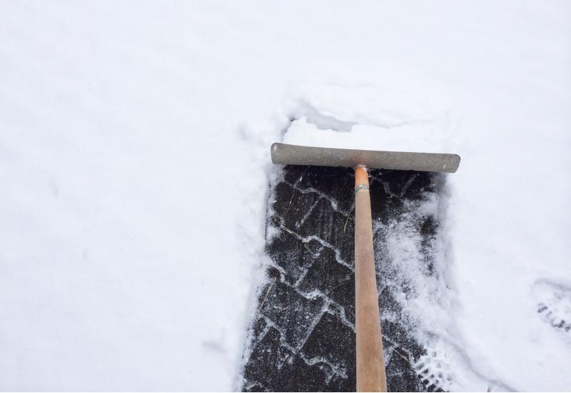 Schnee auf Gehweg wird weggeschippt