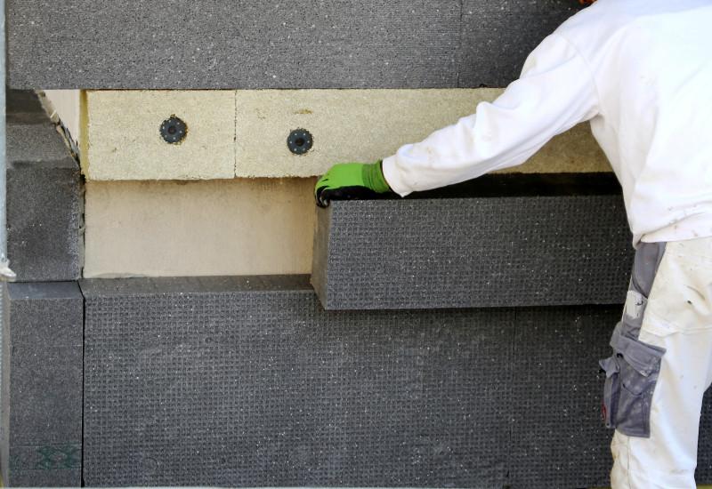 Bauarbeiter bringt Isolierung an einer Hausfassade an.