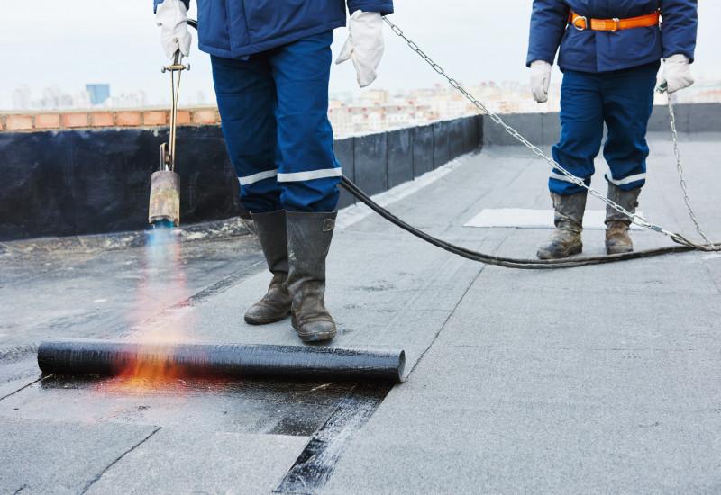 Bauarbeiter verlegen bitumenhaltige Dachbahnen.
