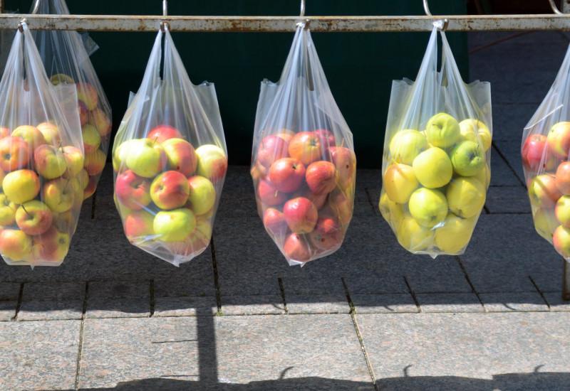 an einer Eisenstange über einem gepflasterten Platz oder Fußweg hängen durchsichtige Plastiktüten mit Äpfeln