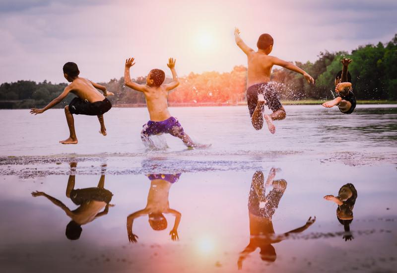 Vier Jungen springen in einen See.