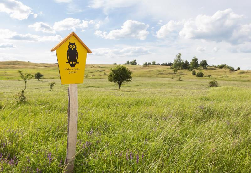Ein Naturschutzgebiet wird mit einem entsprechenden Schild ausgewiesen.