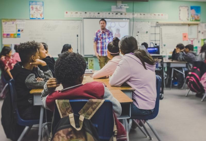 Schüler hören einem Lehrer zu.