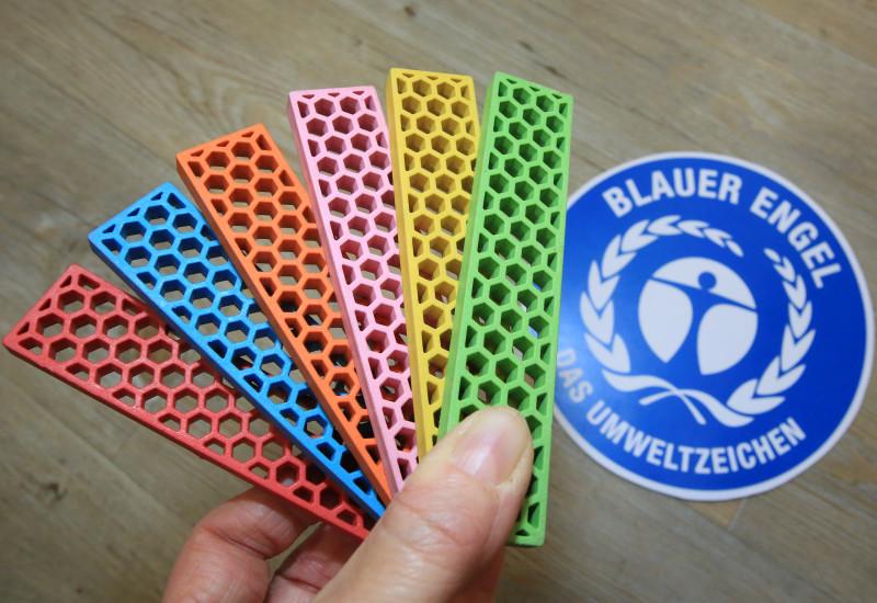 Bioblo-bausteine vor einem Logo des Blauen Engel