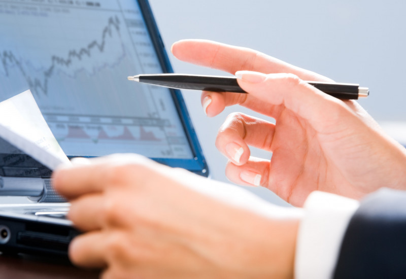 Hands in front of a laptop screen showing a trading picture.