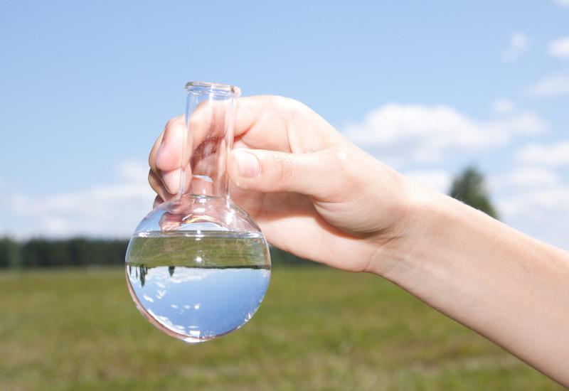 Ein Reagenzkolben vor grüner Wiese, darin Wasser.