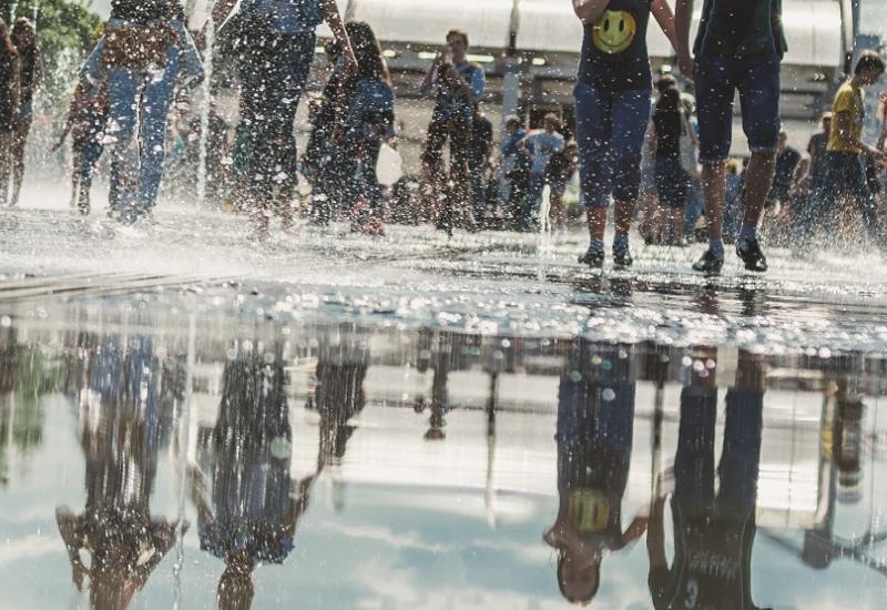 Das Bild zeigt eine Wasserfläche in einer Stadt, offensichtlich ein Brunnen. Es laufen mehrere Menschen über die Wasserfläche und spiegeln sich darin.