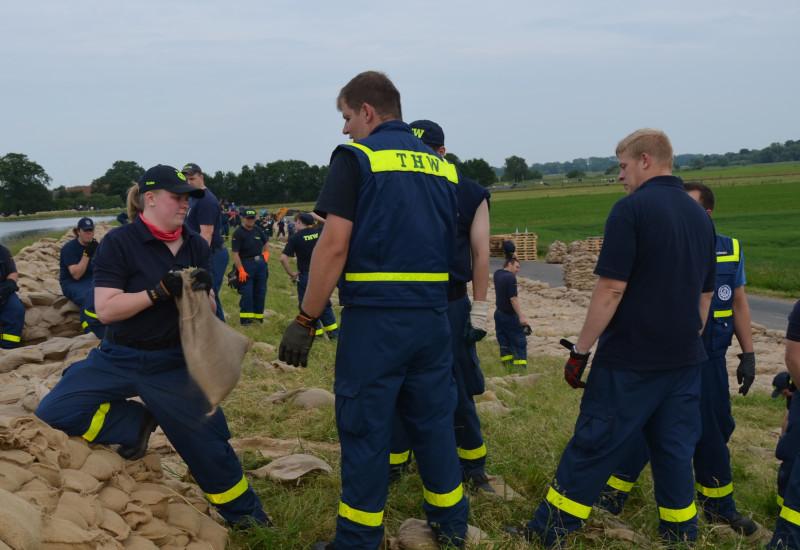 THW Mitglieder bauen einen Deich aus Sandsäcken