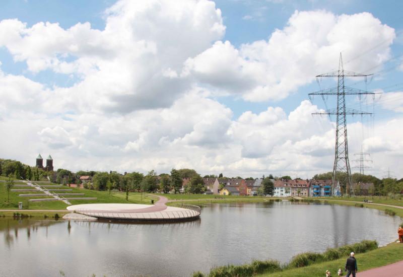 Das Bild zeigt einen angelegten kleinen See mit Grünanlagen und Häusern im Hintergrund