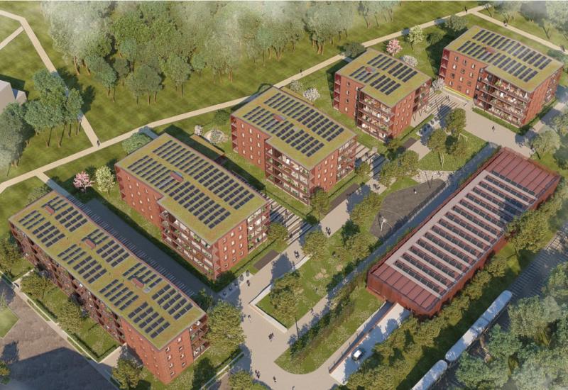 Vier Häuserblocks mit Fotovoltaik und Gründach aus der Vogelperspektive