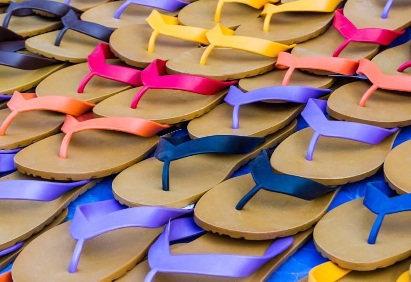 Abgebildet sind mehrere gestapelte Paar Flipflops in verschiedenen Farben.