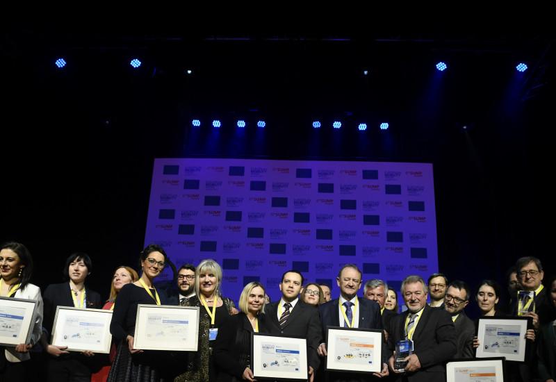 Alle Finalistinnen und Finalisten stehen gemeinsam auf der Bühne und die Preisträgerkommunen zeigen ihre Preise