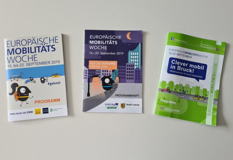 Drei Programmhefte der Europäischen Mobilitätswoche in unterschiedlichem Design aus Essen, Leipzig und Fürstenfeldbruck