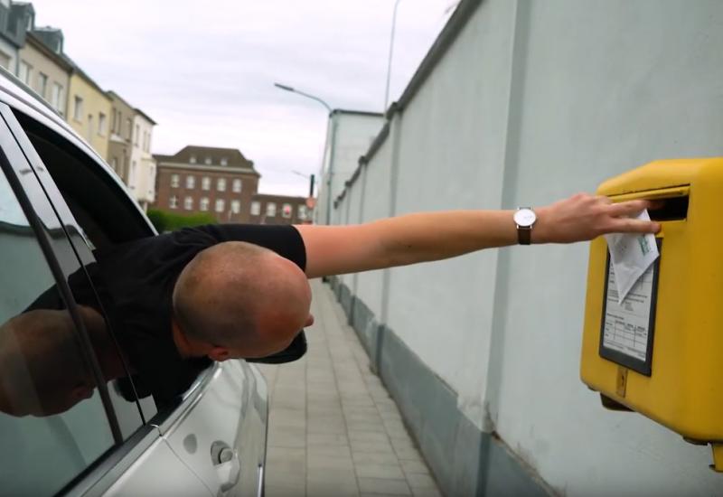 Fahrer versucht aus Autofenster einen Brief in einen Briefkasten zu werfen