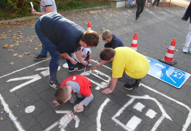 """Eltern und Kinder malen das Straßenschild """"verkehrsberuhigter Bereich"""" auf den Asphalt"""