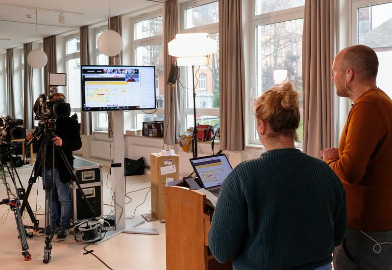 Zwei Moderatoren gucken in die Kamera und auf einen Bildschirm, während Sie das Netzwerktreffen moderieren.