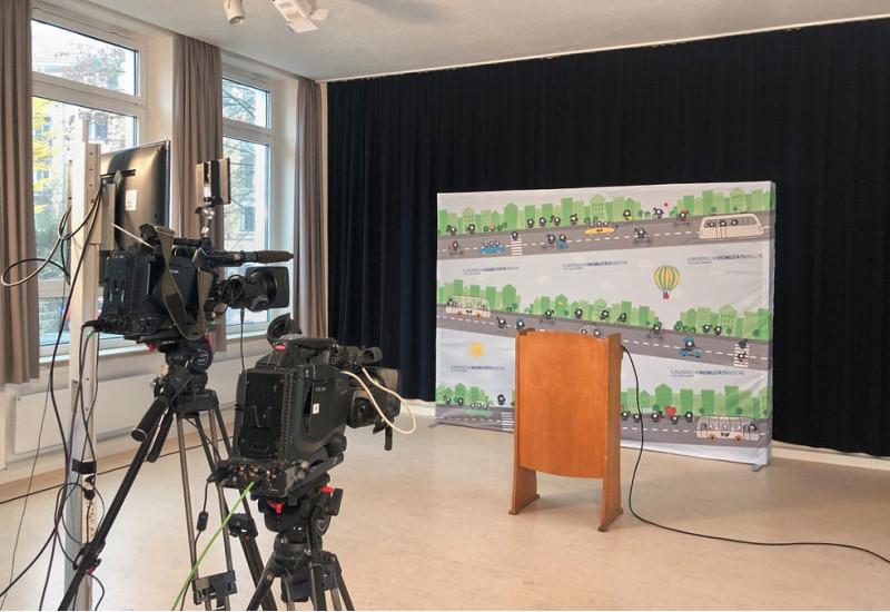 Es sind ein leeres Podium, eine Messewand mit EMW-Logo sowie ein eine Kamera, die das Setting filmt zu sehen.