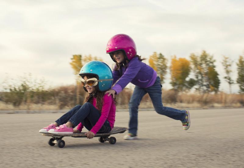 Ein Kind mir Helm schiebt ein anderes Kind mit Helm auf einem Skateboard.